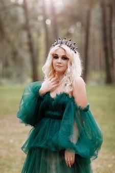 Jonge mooie blonde haren vrouw koningin. prinses loopt. herfst groen bos mysticus. vintage middeleeuwse glanzende kroon.