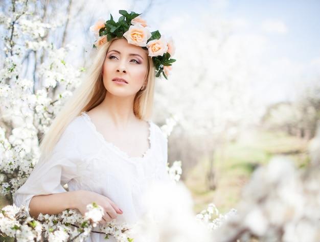 Jonge mooie blonde lachende vrouw in witte jurk en roze krans