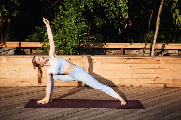 Jonge mooie blonde meisje beoefenen van yoga buiten bij zonsopgang.