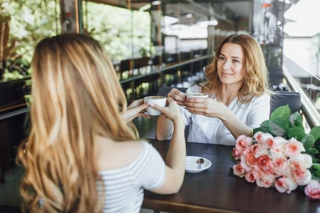 Jonge mooie blonde meisje en haar moeder rusten op een zomerterras café, drinken koffie en communiceren. ze zijn vrolijk en grappig.
