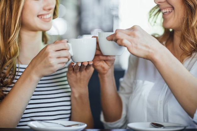 Jonge mooie blonde meisje en haar moeder rusten op een zomerterras café, koffie drinken en communiceren.