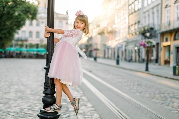 Jonge mooie blonde meisje in modieuze elegante roze jurk, poseren voor de camera buiten in de oude europese stad, vintage straat lamp, zonsopgang op de achtergrond knuffelen