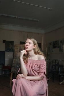 Jonge mooie blonde meisje in roze jurk propping haar hoofd met arm.