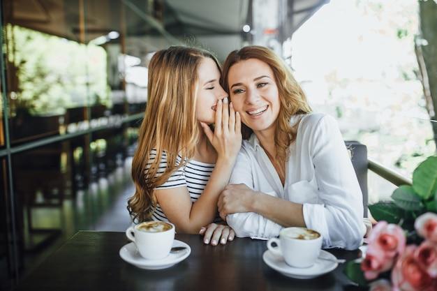 Jonge mooie blonde meisje spreekt met haar moeder een interessant geheim, ze zitten op een zomerterras cafe, gelukkig en lachen.