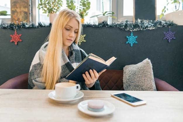 Jonge mooie blonde meisjeszitting in de lezingsboek van de koffiewinkel