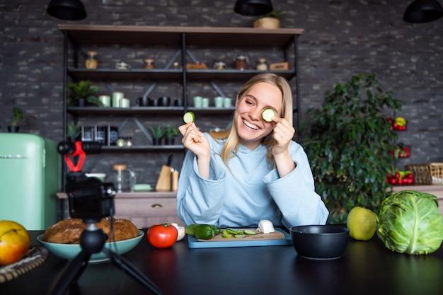Jonge mooie blonde neemt video's op terwijl ze kookt in de keuken