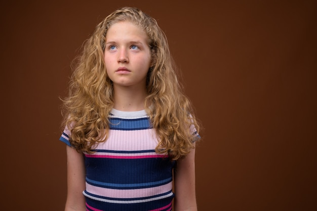 Jonge mooie blonde tiener die op bruin denkt