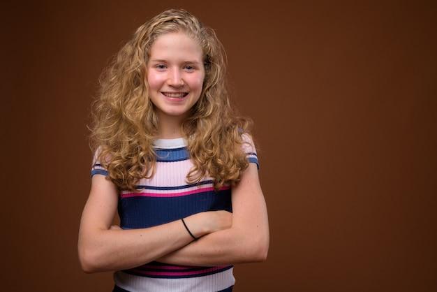 Jonge mooie blonde tiener die op bruin glimlacht
