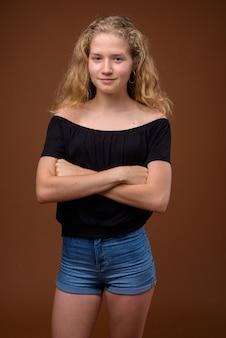 Jonge mooie blonde tiener op bruin