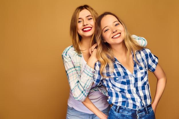Jonge mooie blonde twee die in trendy de zomer geruite overhemden glimlacht