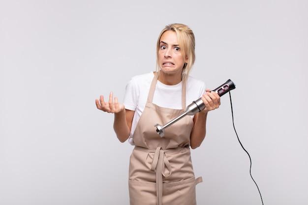 Jonge mooie blonde vrouw bakker met een mixer