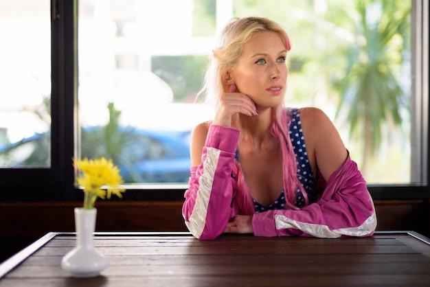 Jonge mooie blonde vrouw denken en ontspannen in de coffeeshop