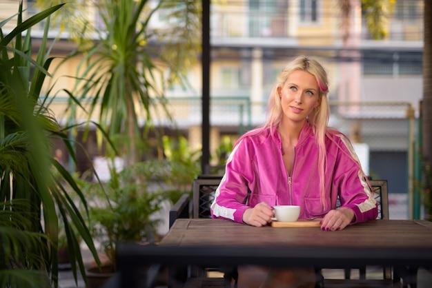 Jonge mooie blonde vrouw denken zittend in de coffeeshop