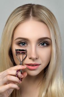Jonge mooie blonde vrouw die de spiegel bekijkt en een wimperkruller houdt
