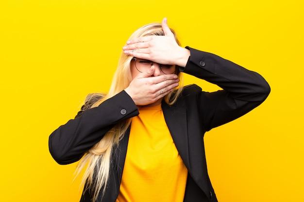 Jonge mooie blonde vrouw die gezicht behandelt met beide handen die nee tegen de camera zegt! afbeeldingen weigeren of foto's verbieden tegen een gele muur