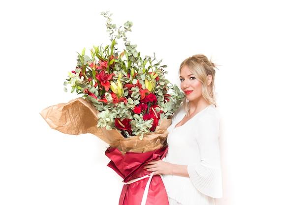 Jonge mooie blonde vrouw die groot boeket van kleurrijke bloemen houdt tegen de muur