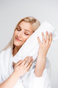 Jonge mooie blonde vrouw die in badjas handdoek koestert