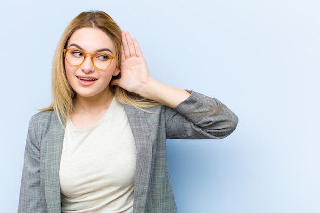 Jonge mooie blonde vrouw die lacht, nieuwsgierig naar de zijkant kijkt, probeert te luisteren naar roddel of een geheim afluistert tegen een vlakke muur