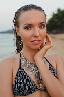 Jonge mooie blonde vrouw die op zandstrand in bikini zwemmend kostuum, uitstekende halsband zonnebaden
