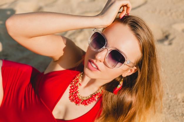Jonge mooie blonde vrouw die op zandstrand in rood zwemmend kostuum, zonnebril zonnebaden