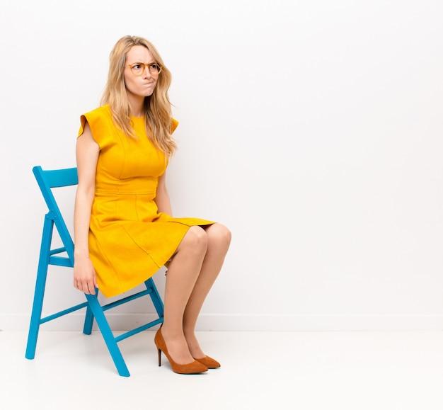 Jonge mooie blonde vrouw die verbaasd en verward kijkt, zich afvraagt of probeert een probleem op te lossen of tegen een egale kleurenmuur denkt