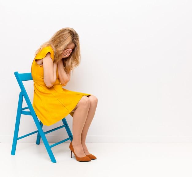 Jonge mooie blonde vrouw die zich verdrietig, gefrustreerd, nerveus en depressief voelt, gezicht bedekt met beide handen, huilend tegen een egale kleurmuur