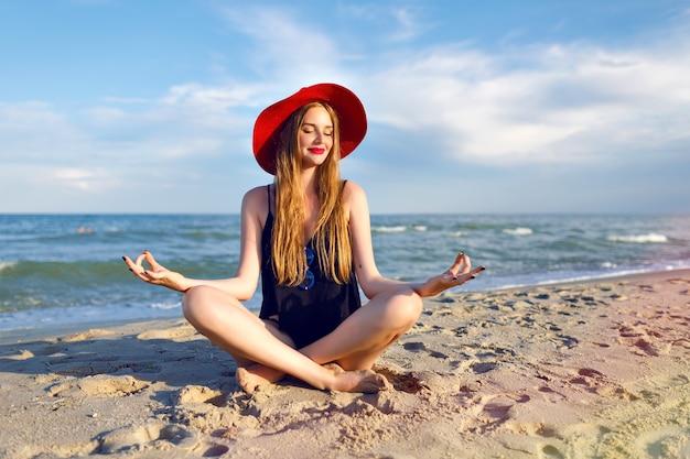 Jonge mooie blonde vrouw, gekleed in zwarte bikini, slank lichaam, geniet van vakantie en plezier maken op het strand, lange blonde haren, zonnebril en strooien hoed. vakantie op bali.