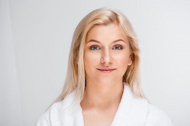 Jonge mooie blonde vrouw in badjas glimlachen