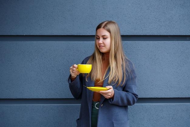 Jonge mooie blonde vrouw in een grijze jas drinkt hete thee uit een gele kop op een koude herfstdag. heerlijk warm drankje op het terras in het café