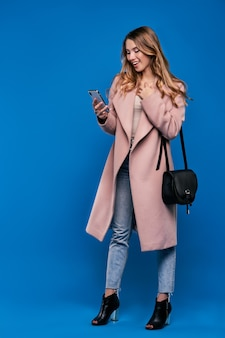 Jonge mooie blonde vrouw in een regenjas op een blauwe muur met mobiele telefoon