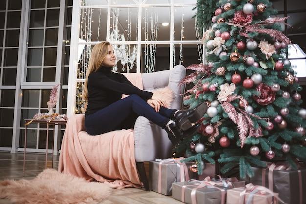 Jonge mooie blonde vrouw in een zwarte trui met speelgoed in haar handen in de buurt van de kerstboom met geschenken. new year's infusie meisje siert een kerstboom. nieuwjaar