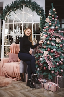 Jonge mooie blonde vrouw in een zwarte trui met speelgoed in haar handen in de buurt van de kerstboom met geschenken.