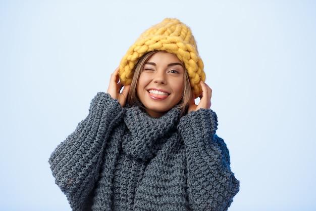 Jonge mooie blonde vrouw in gebreide muts en trui glimlachend knipogen op blauw.