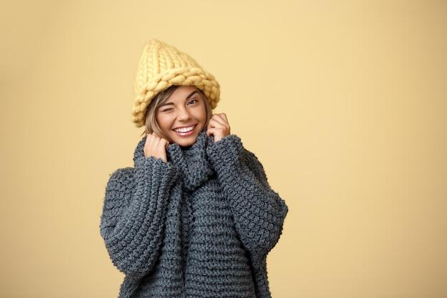 Jonge mooie blonde vrouw in gebreide muts en trui glimlachend knipogen op geel.