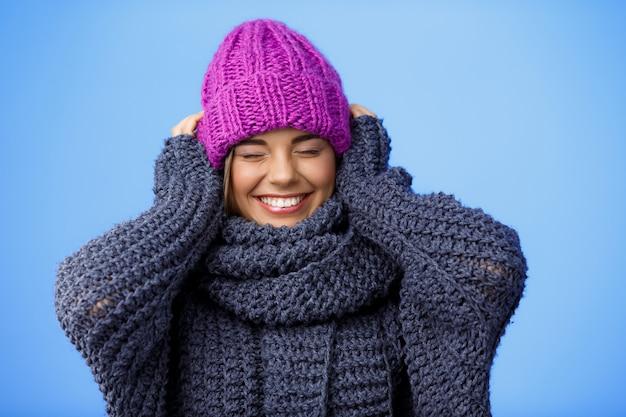 Jonge mooie blonde vrouw in gebreide muts en trui lachend op blauw.