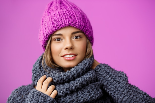 Jonge mooie blonde vrouw in gebreide muts en trui lachend op violet.