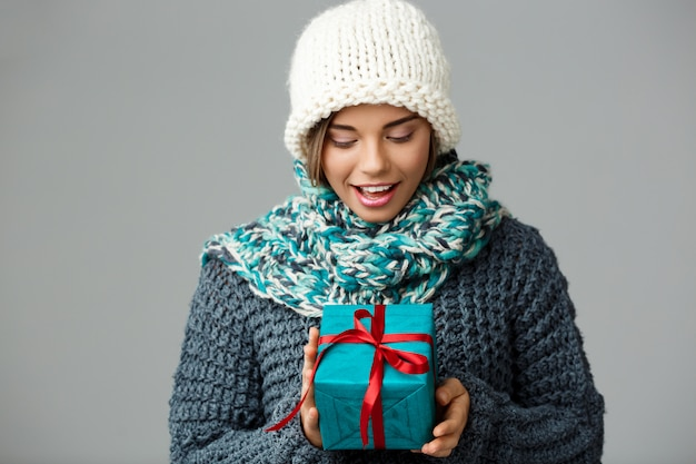 Jonge mooie blonde vrouw in gebreide muts sweater en sjaal glimlachend bedrijf geschenkdoos op grijs.