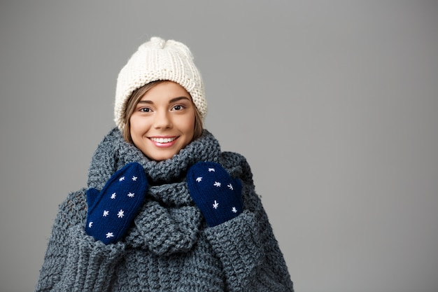 Jonge mooie blonde vrouw in gebreide muts sweater en wanten glimlachend op grijs.
