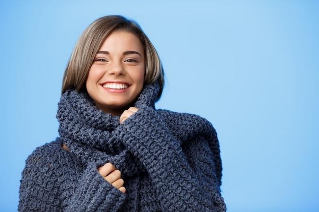 Jonge mooie blonde vrouw in hoed en trui lachend op blauw.
