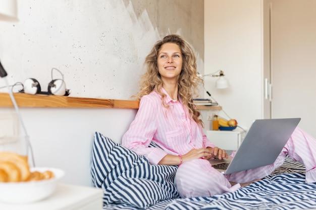 Jonge mooie blonde vrouw in roze pyjama zittend op bed bezig met laptop, freelancer thuis