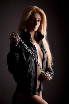 Jonge mooie blonde vrouw in sexy slipje, leren jas en kettingen op lichaam permanent over grijze achtergrond