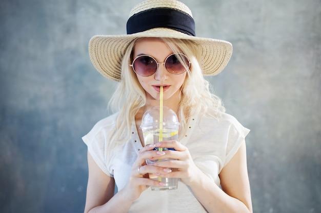 Jonge mooie blonde vrouw in strohoed. zonnebril in zomerstijl.