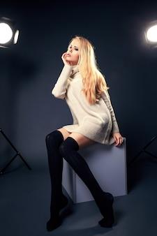 Jonge mooie blonde vrouw in warme gebreide handgemaakte kleding. model mode schieten. herfst, winterseizoen.