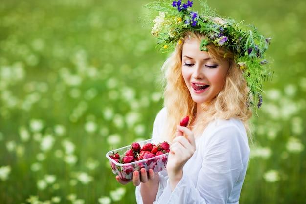 Jonge mooie blonde vrouw in witte jurk en bloemen krans houden doos verse aardbeien op zomerdag