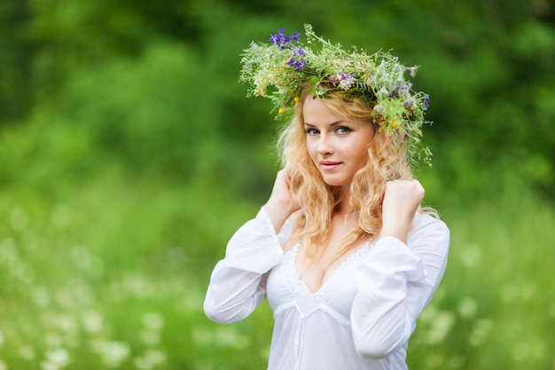 Jonge mooie blonde vrouw in witte jurk en bloemen krans permanent en camera kijken op zomerdag