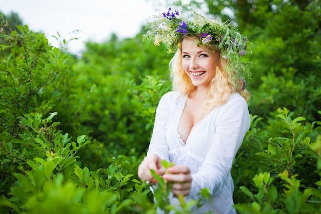 Jonge mooie blonde vrouw in witte jurk en bloemen krans permanent en lachend op zomerdag