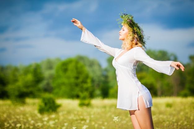 Jonge mooie blonde vrouw in witte kleding en kroon die zich met gesloten ogen bevinden en van zonneschijn op de zomerdag genieten