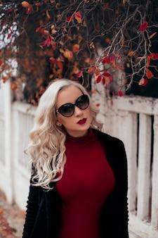 Jonge mooie blonde vrouw in zwarte jas op herfst park