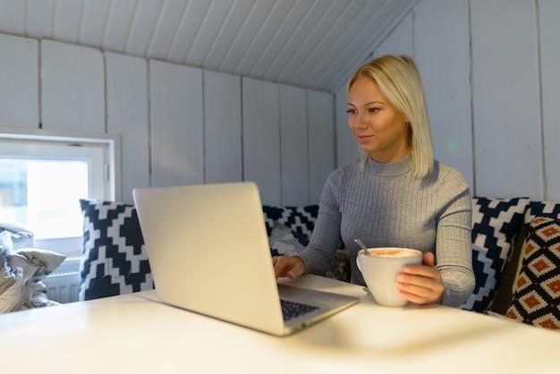 Jonge mooie blonde vrouw koffie drinken tijdens het gebruik van laptop thuis