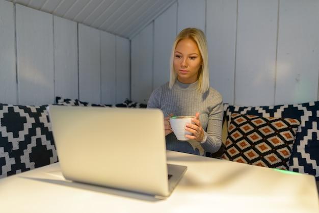 Jonge mooie blonde vrouw koffie drinken tijdens het kijken naar laptop thuis